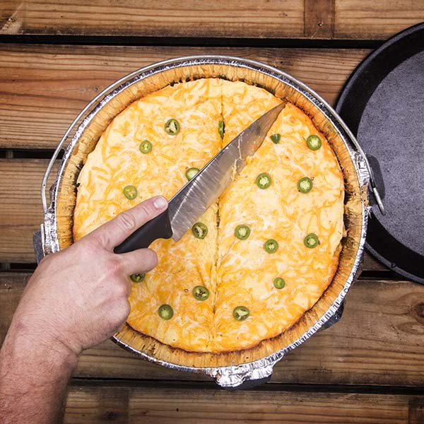 Cutting generous slices from a Chicken Enchilada Pie in a Dutch oven.