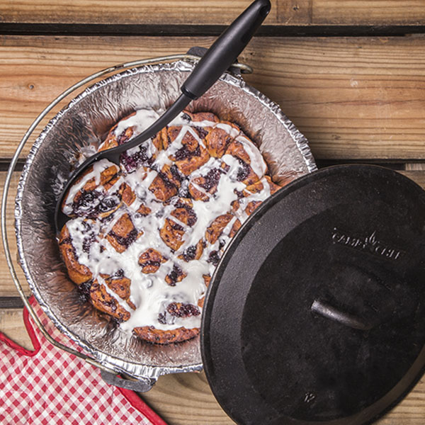 Fresh off the fire and frosted Dutch Oven Blueberry Cinnamon Rolls served on a picnic table.