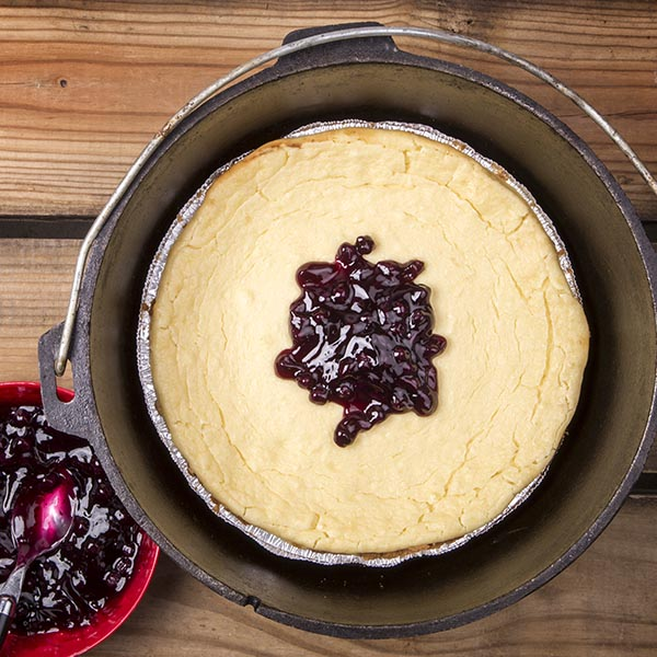 Dutch oven cheese cake is delicious and surprisingly easy to make when you use a premade crust in an aluminum foil pie tin.