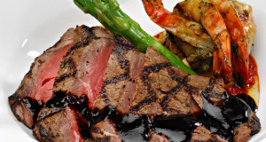 Sliced steak topped with a red wine reduction sauce, plated alongside fresh green asparagus spears and prawns.