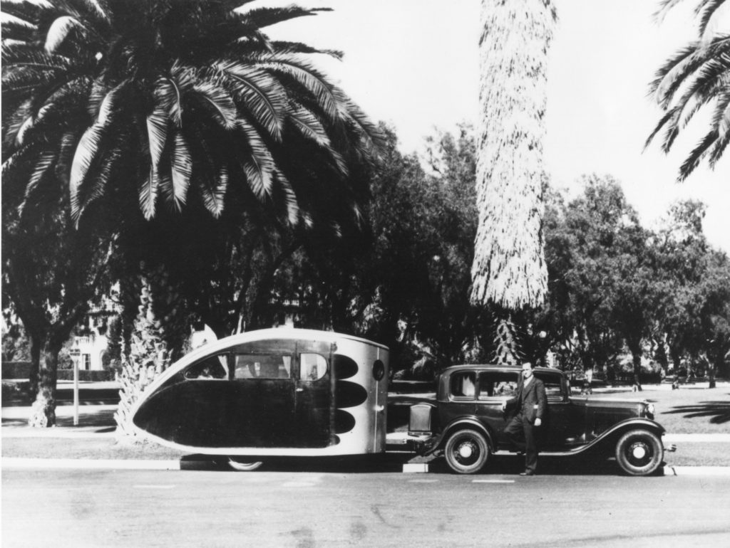 """This photo shows an early Airstream trailer, probably created around 1933. This man appears to be Wally Byam even though he is not identified. The early Airstream trailers were shaped like a """"teardrop"""" to improve aerodynamic efficiency, and the sleeping compartment in this model sits toward the rear of the trailer."""