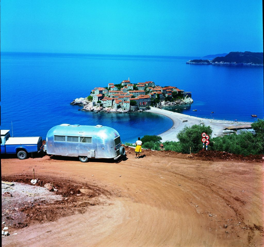 An Airstream allows you to travel to places that you couldn't reach by plane or train. In this photo, a traveler observes Sveti Stefan, an island about 4 miles southeast of Budva that is connected by causeway to the mainland in Montenegro.