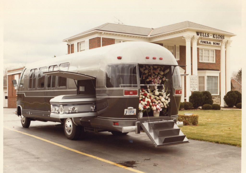 This is an exterior view of an Airstream Funeral Coach around 1982. The flowers were put in the back and the casket was put in a side carrier space. Mourners could ride inside the passenger space - with individual seats and a couch.