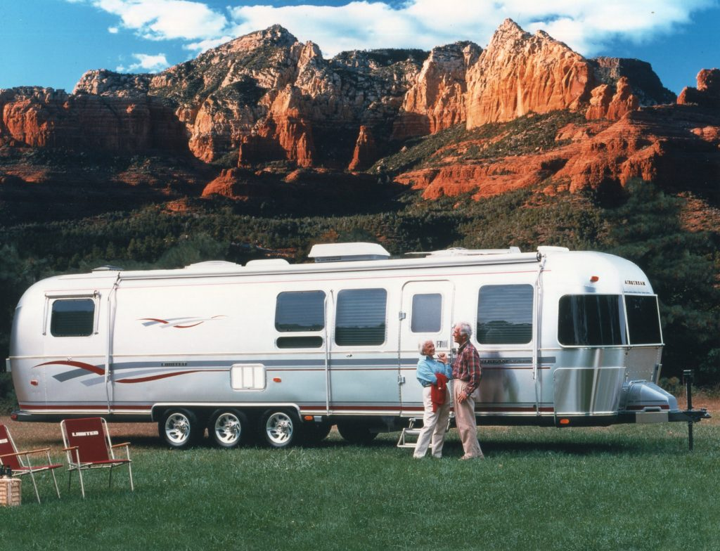 The most luxurious Airstream trailer, the Limited, even came with branded folding chairs. The couple in this photo look happy as they camp near a beautiful mountain range.