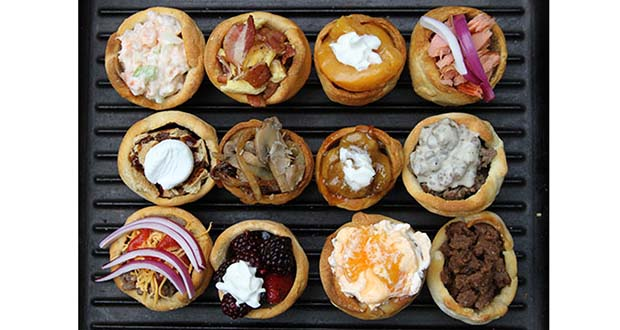 Display of 12 different campfire biscuit cup fillings on cast iron Dutch Oven lid.