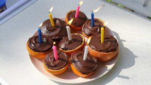 Campfire birthday cake cupcakes in citrus halves - oranges and grapefruit - with candles lit, ready for the party to begin.