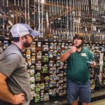 Clint gets a lesson in bass fishing from an associate at Bass Pro Shops at the Pyramid in Memphis, Tennessee prior to trying his luck at Natchez State Park later in the 50 Campfires Field Trip: Great River Road.