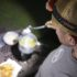 Nick frying fish in tempura batter on picnic table with COAST headlamp during Field Trip: Great River Road.