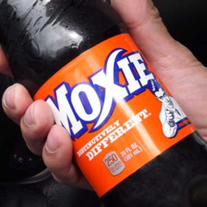 Close up of a label on a bottle of Moxie - the official soft drink of Maine. Even they admit it's an acquired taste.