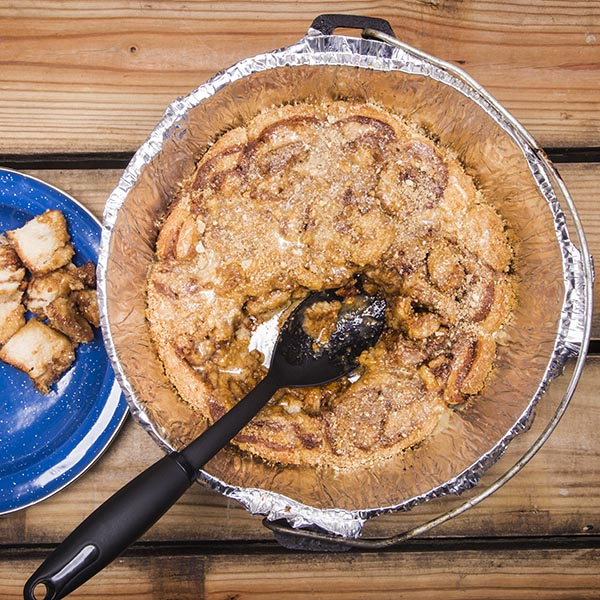 Can't decide between cinnamon rolls or caramel rolls for camping breakfast? With this super easy Dutch Oven Gooey Caramel Cinnamon roll recipe, you can have both!