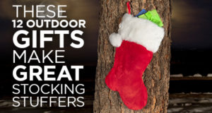 A Christmas stocking hung outdoors on a tree trunk.