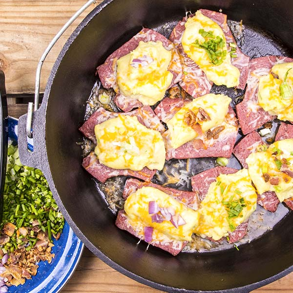 Dutch Oven stuffed sausage and potato boats in a Camp Chef Dutch oven with garnishes on the side.