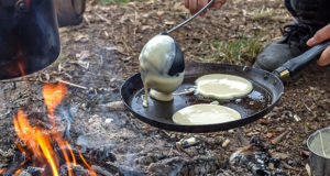 Mesquite pancakes cooking over open campfire.