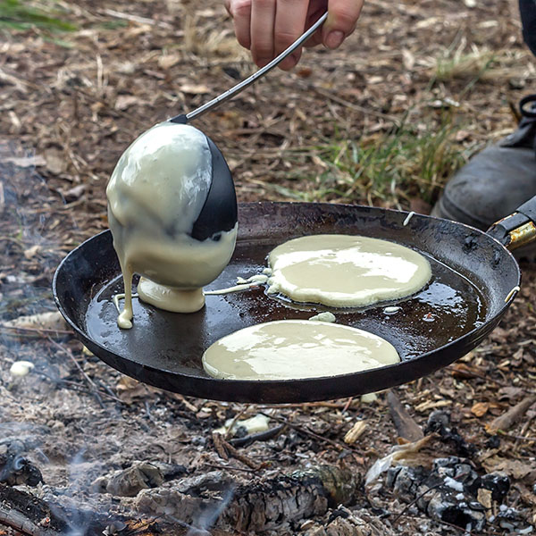 Mesquite pancakes cooking on skillet griddle over open fire coals.