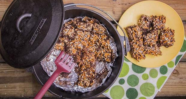 A plate of 7 Layer Brownie Bars sitting next to more in a Dutch oven.