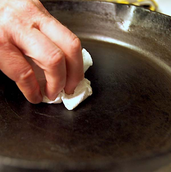Next step to clean, care for cast iron is, dump out the water and dry your cast iron Dutch oven or skillet with a paper towel.