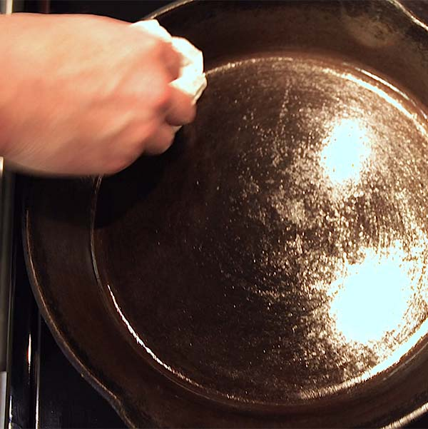 Finally, with another paper towel, wipe away excess oil from the surface to clean, care for cast iron Dutch oven or skillet.