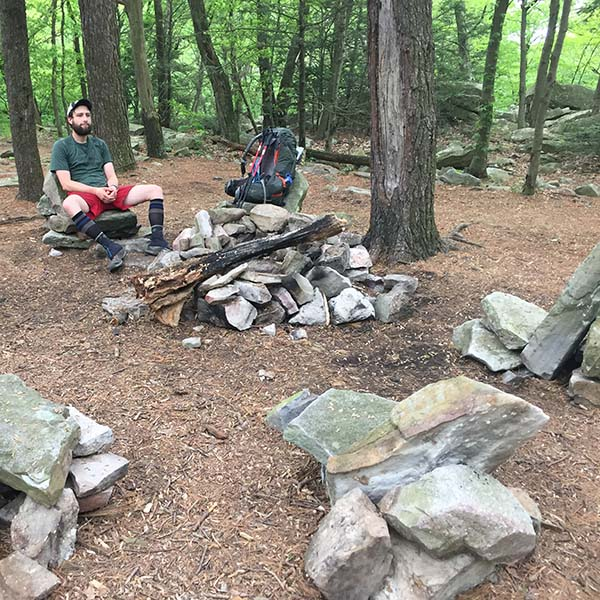 Owen Rachampbell of Darn Tough taking a rest in Pennsylvania where someone had built stone lounge chairs around a fire pit.
