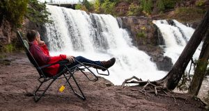 person relaxing in camping chair