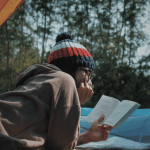 reading a book at the campsite