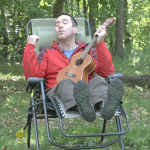 playing ukulele in a camping chair